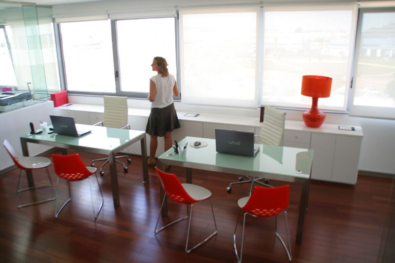 Mesas de oficina en acero inoxidable con encimera de cristal lacado blanco.