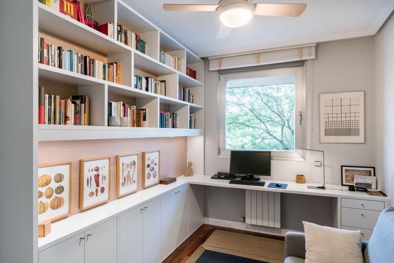 Zona de estudio en casa con libreria blanca con trasera roble y mesa con cajonera. Todo acabado en sintético.